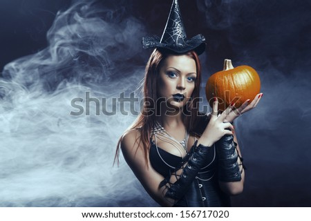 The serious girl is standing with the pumpkin in smoke