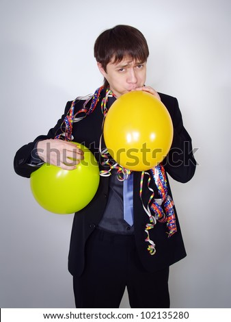 The serious man in a business suit inflates balloons. Party at office
