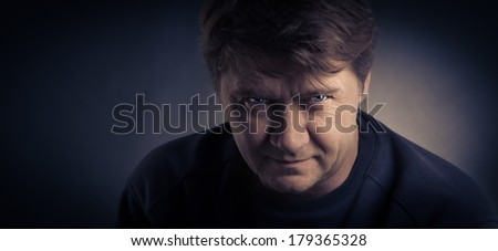 The serious young man on a dark background.