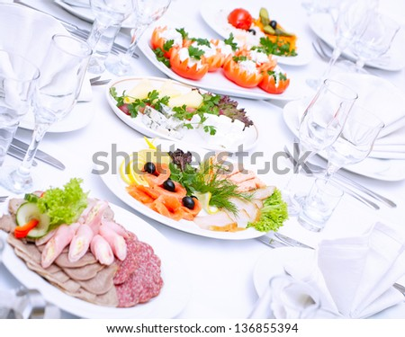 The served dinner table in a restaurant. Cold blue light. - stock photo