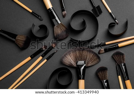 The set of brushes for applying make-up of different usage: for lips, eyes, lashes, skin, brows. Professional equipment of make-up artist. Spiral curls of black carton create artistic atmosphere. - stock photo