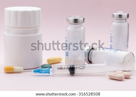 The set of medicine pill bottle and injection syringe on pink background - stock photo