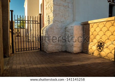 The setting sun casts a moody shadow of a cross and ironwork on an adobe wall at an historic Spanish mission - stock photo