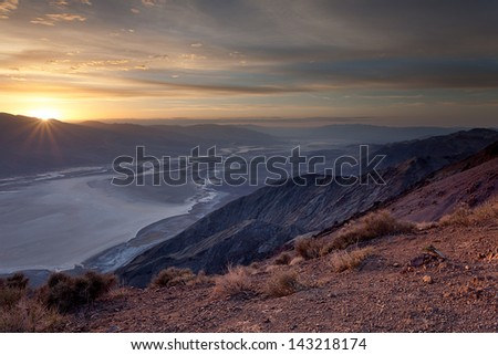 The setting sun casts sunbeams over Badwater Basin salt flats in Death Valley, CA.  Taken from Dante's View. - stock photo