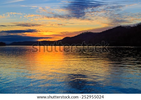 The setting sun silhouettes hills as it reflects upon the waters of the Ohio River as seen from Paden City, West Virginia. - stock photo