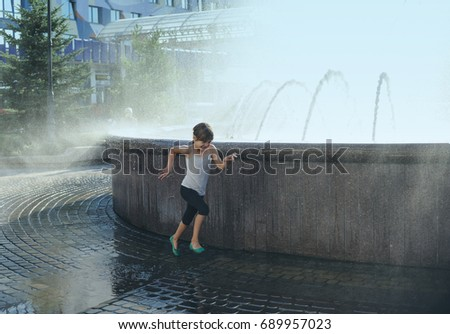 The seven-year-old girl is running in a splash of fountain water.