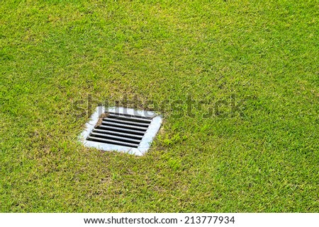 The sewer grate on the lawn - drainage for heavy rain - stock photo
