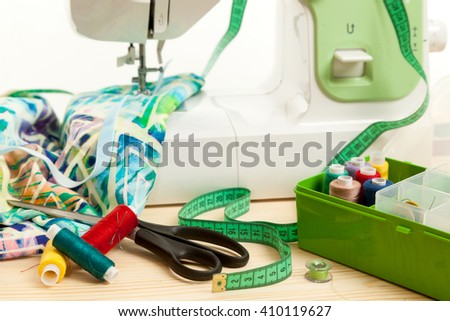 the sewing machine with a measuring tape and accessories costs on a table