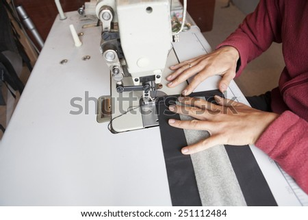 the sewing process - Women's hands behind her sewing - stock photo