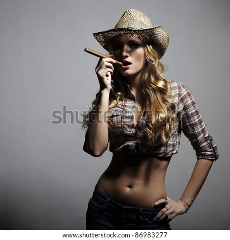 The sexy blonde woman with amazing hair in a hat and with a cigar in an image of the American cowboy. Fashion portrait.