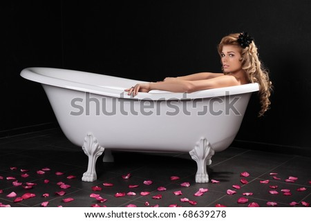 The sexy girl lies in a white bath on a black background - stock photo