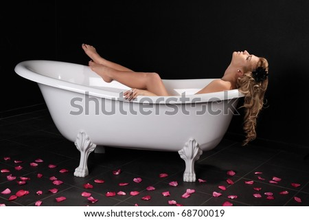 The sexy girl lies in a white bath on a black background