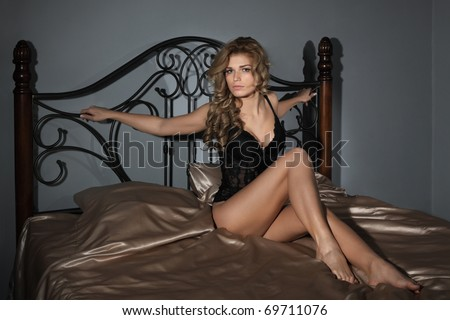 The sexy girl sits on a bed - stock photo