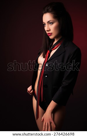 The sexy young woman in a black jacket with a red tie, with a red luminescence, on a black background