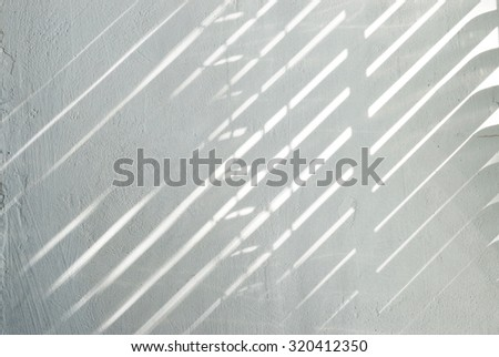 The shadow from jalousie on white wall - stock photo