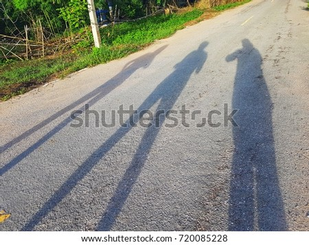 The shadow is caused by the morning sun. It is the shadow of three different women, a middle-aged child.