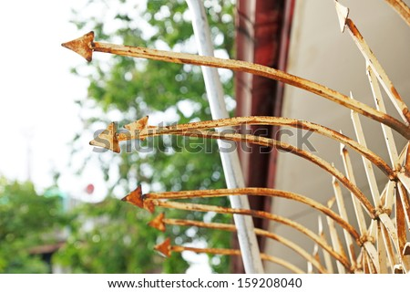 The sharp steel arrows on fence top to protecting property. - stock photo