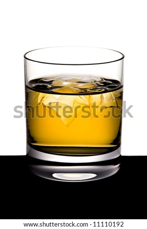 The shined glass of whisky with ice stands on a black table