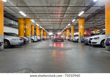 The shined underground garage with the moving cars and parked cars - stock photo