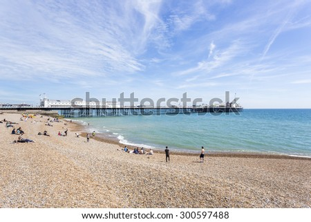 The shingle beach at Brighton, East Sussex, UK in summer and the Palace Pier (Brighton Pier) on a sunny day - stock photo