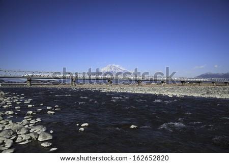The Shinkansen passing through Mt. Fuji and the Fujikawa bridge - stock photo