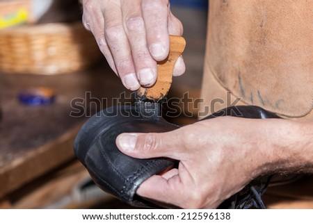 the shoemaker puts shoe polish - stock photo