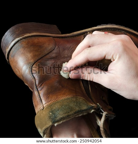 The shoemaker puts shoe polish on black background - stock photo