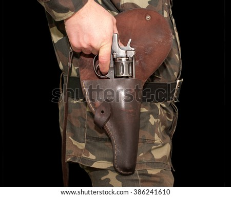 The shooter in camouflage ready to fire from an old revolver, which pulls from the holster on his belt, isolated on black background - stock photo