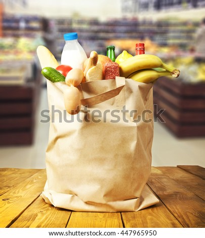 The shopping bag with food and drinks stands on the table and blurred supermarket on the background - stock photo