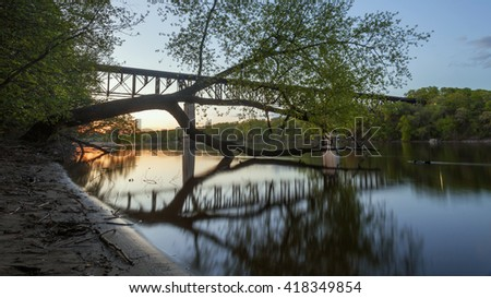 The Short Line Bridge and Trees Reflect in the Mississippi River at Dusk in this Generic Looking Minnesota Landscape - stock photo