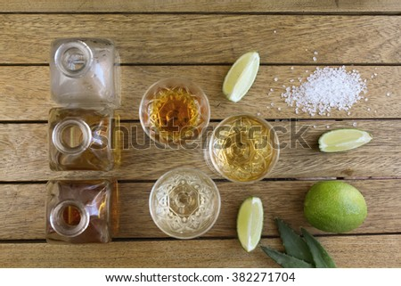 The shots of various drinks next to square unlabelled bottles with lime and salt on a wooden surface viewed from above - stock photo