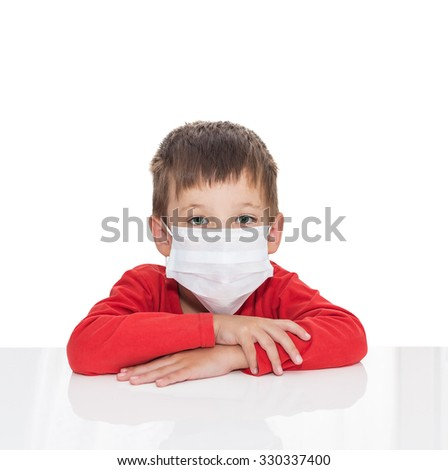 The sick five-year-old boy sits at a white table with medicine healthcare mask for is protection again virus, isolated on a white background - stock photo