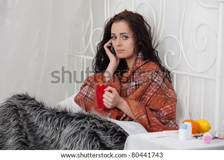 The sick unhappy young woman lies in a bed. Call of the doctor on the house. - stock photo
