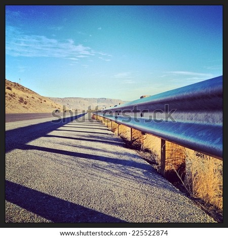 The side of a road with metal barriers. - stock photo