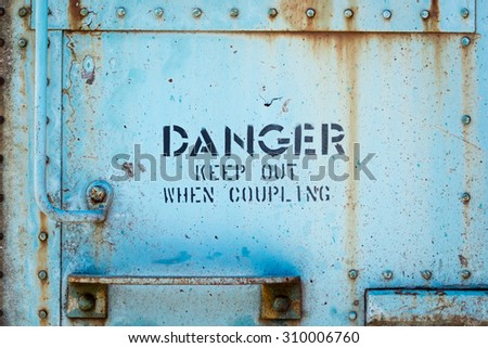 "The side of a train car with the word ""Danger keep out when coupling""."