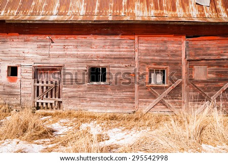 The side of an old barn is exposed with snow present - stock photo