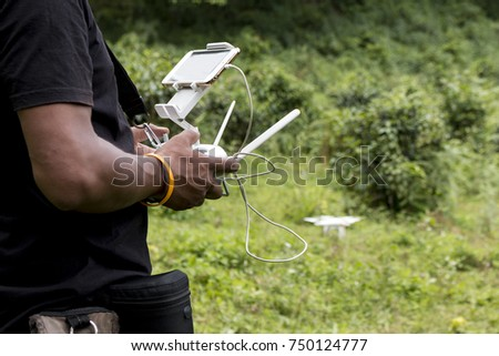The side view of man holding drone controller with mobile phone. drone flying over trees,blurred background.