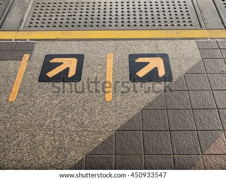 The Sign of yellow arrow on floor at train station