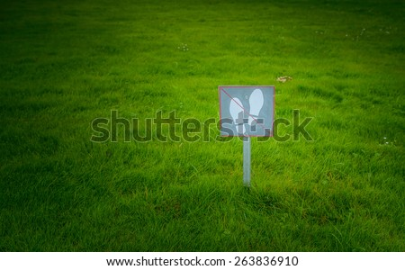 "The sign on the label ""do not walk"" on a green lawn. - stock photo"