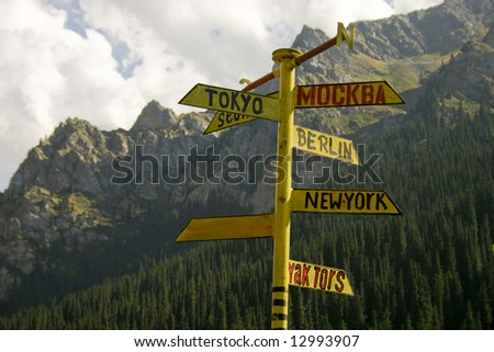 The signpost from meta indicating a managements seven large cities of the world, on a background of mountains. - stock photo