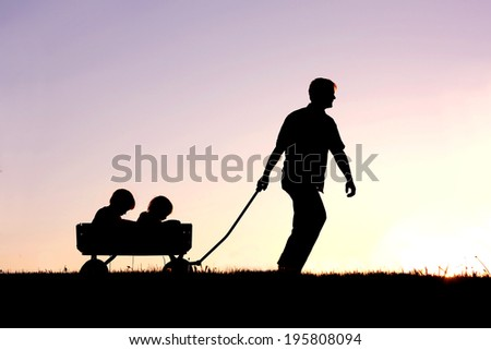 The silhouette of a father pulling his two young children behind him in a wagon isolated in front of a sunset in the sky. - stock photo