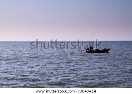 The silhouette of a fisherman with his boat in the sea