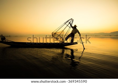 The silhouette of a fishing boat with Myanmar. - stock photo