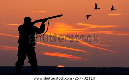 the silhouette of a hunter on sunset background - stock photo