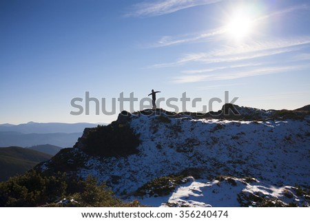 The silhouette of a man in the mountains against the blue sky.