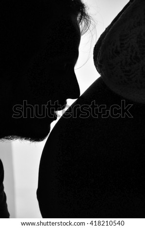 The silhouette of a man kissing the belly of a pregnant women. - stock photo