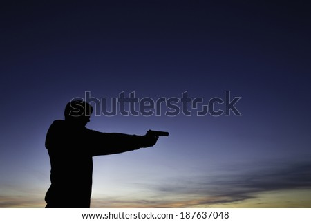 The silhouette of a man, wearing a hoodie, aiming a pistol, outside, during a sunset. - stock photo