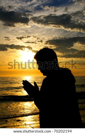The silhouette of a man with his hands folded in prayer at the ocean at sunset.