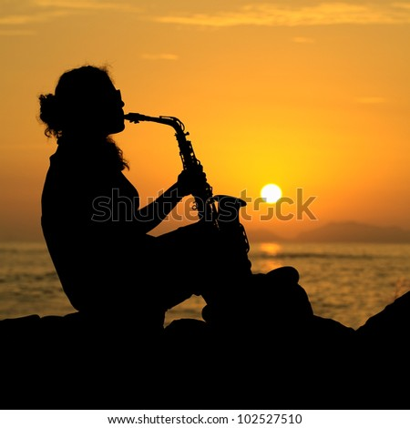 The silhouette of a young female musician playing her saxophone on the coast at sunset - stock photo