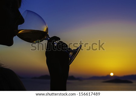 The silhouette of a young woman drinking wine in a sunset over looking the Aegean Sea and islands, Turkey / silhouette of woman drinking wine at sunset